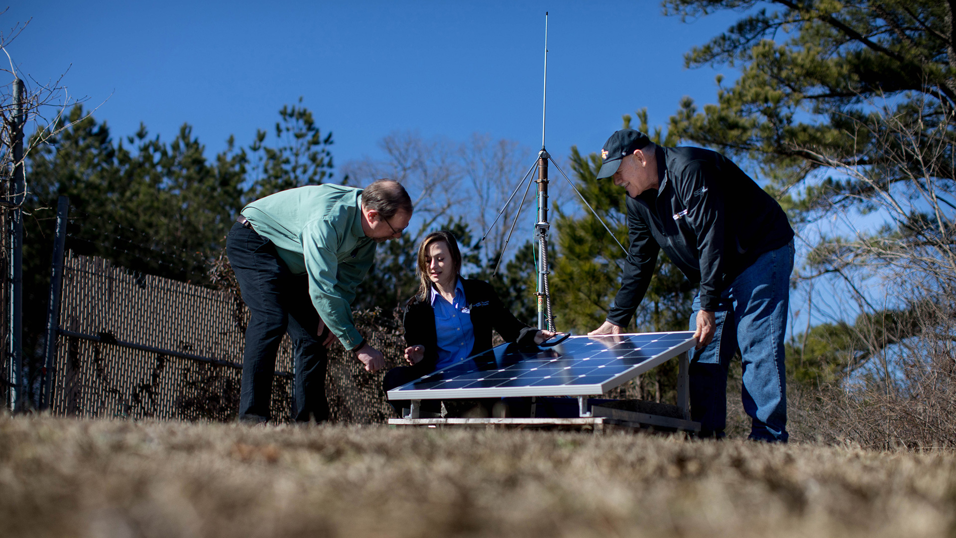 photo: two men and one woman, working outdoors in a field on a crisp Fall day, examine weather equipment.