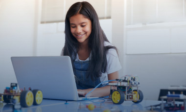 Female student sitting at a computer building and programming robot vehicle